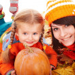 Happy family with pumpkin on autumn leaves. — Стоковое фото