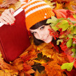 Girl in autumn orange leaves with book. — Stock Photo #6725253