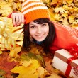 Girl in autumn orange hat on leaf group. — Stock Photo #6725258