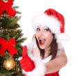 Christmas girl in santa hat and fir tree with thumb up. — Stock Photo #6725268