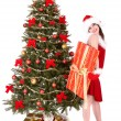 Christmas girl in santa hat and fir tree with red gift box. — Foto de Stock