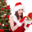 Christmas girl in santa hat and fir tree with red gift box. — Stockfoto