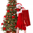Girl in santa hat holding shopping bag, — Stock Photo