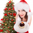 Royalty-Free Stock Photo: Girl in red santa hat eating cake on plate.