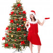 Girl in santa hat by christmas tree. — Stock Photo
