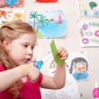 Child with scissors cut paper in play room. — Foto de Stock