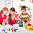 Children with teacher painting play room. — Stock Photo