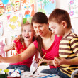 Children with teacher draw paints in play room. — Stock Photo #6725708