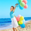 Child playing with balloons at the beach — Stock Photo #6725773