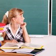 Schoolchild in classroom near blackboard. — Stock Photo