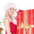 Royalty-Free Stock Photo: Girl in santa hat holding  gift box by christmas tree..