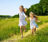 Kids running across green grass outdoor. — Stock Photo