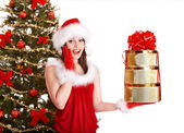 Christmas girl in santa hat holding stack gift box. — Stock Photo