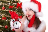 圣诞女孩在圣诞老人的帽子和杉木树中与闹钟. — 图库照片