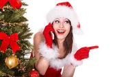 Garota em santa chapéu chamada celular pela árvore de natal. — Foto Stock