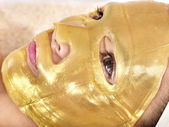 Girl with gold facial mask. — Stock Photo