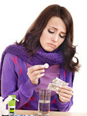 Girl holding glass of water and taking pills. — Stockfoto