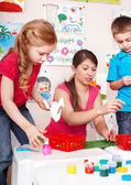 Child with teacher in play room. — Stock Photo