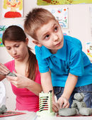 Child mould from clay with teacher. — Stock Photo