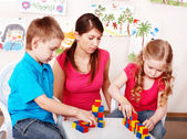 Child with wood block in play room. — Stock Photo