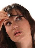 Aplikace make-upu. řasenka je kladen na horní řasy. — Stock fotografie