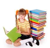 Schoolgirl reading pile of books. — Stock Photo