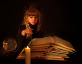 Child reading magic book at candle. — Stock Photo