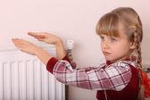 Mädchen wärmen die hände in der nähe von kühler. krise. — Stockfoto