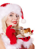 Christmas girl in santa hat eat cake on plate. — Stock Photo