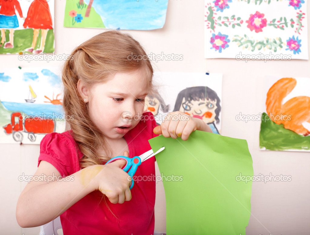 Little girl  with scissors cut paper at home. — Stock Photo #6725673