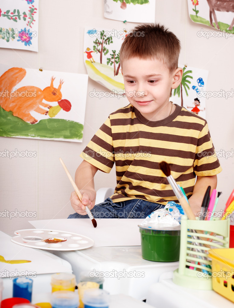 Child with brush draw picture  in play room. Preschool. — Stock Photo #6725711