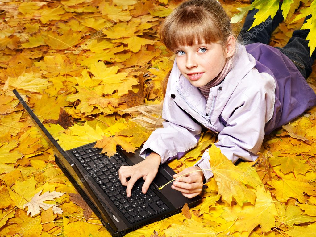 Childl in autumn leaves with laptop and books. Outdoors. — Stock Photo #6725887