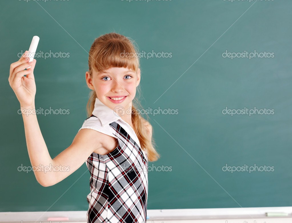 Happy schoolchild writing on blackboard.  Stock Photo #6725940