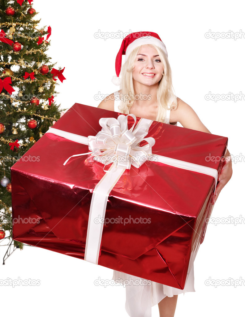 Girl in santa hat giving red gift box by christmas tree. Isolated. — Stock Photo #6726337