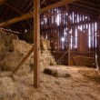 Interior of old barn with straw bales - Stock Photo