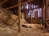 Interiér staré stodoly s balíky slámy — Stock fotografie