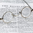 Antique reading glasses on page of bible — Stockfoto
