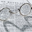 Antique reading glasses on page of bible — Photo