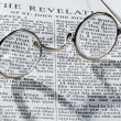 Antique reading glasses on page of bible — Stok fotoğraf
