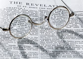 Antique reading glasses on page of bible — Stock Photo