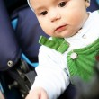 Stock Photo: Baby boy sits in blue perambulator.