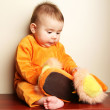 Cute baby boy toddler sitting and holding slippers in hand. — Stock Photo #6452285