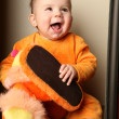 Cute baby boy toddler sitting and holding slippers in hand. — Stock Photo #6452306