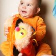 Cute baby boy toddler sitting and holding slippers in hand. — Stock Photo #6452329