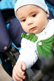 Baby boy sits in blue perambulator. — Stock Photo