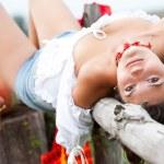 Beautiful brunet woman lie on wooden log. — Stock Photo
