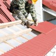 Roofer nailing clay tile - Stock Photo
