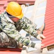 Builder roofer with red tiling - Stock Photo