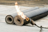 Tar roofing felt roll and blowpipe with flame — Stock Photo