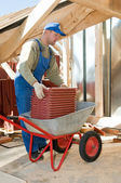 Builder roofer and wheel barrow with clay tile — Stock Photo
